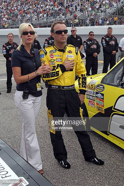Kevin Harvick, driver of the JEGS Chevrolet and his wife DeLana stand on the grid during the performance of the National Anthem prior to the NASCAR...