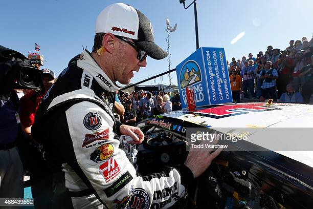 Kevin Harvick driver of the Jimmy John's/ Budweiser Chevrolet puts the winner's sticker on his car after winning the NASCAR Sprint Cup Series...