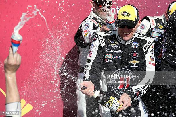 Kevin Harvick driver of the Jimmy John's Chevrolet celebrates with champagne in Victory Lane after winning the NASCAR Sprint Cup Series Good Sam 500...