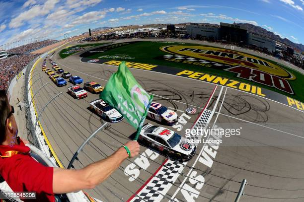 Kevin Harvick driver of the Jimmy John's Ford and Denny Hamlin driver of the FedEx Office Toyota lead the field to green for the start of the Monster...