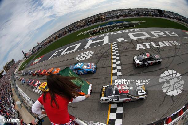 Kevin Harvick driver of the Jimmy John's Ford and Ryan Newman driver of the Caterpillar Chevrolet lead the field to start the Monster Energy NASCAR...