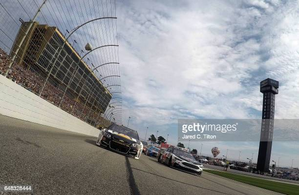 Kevin Harvick driver of the Jimmy John's Ford and Ryan Newman driver of the Caterpillar Chevrolet lead the field under caution prior to the start of...