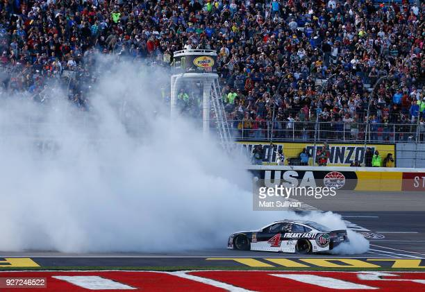 Kevin Harvick driver of the Jimmy John's Ford celebrates with a burnout after winning the Monster Energy NASCAR Cup Series Pennzoil 400 presented by...