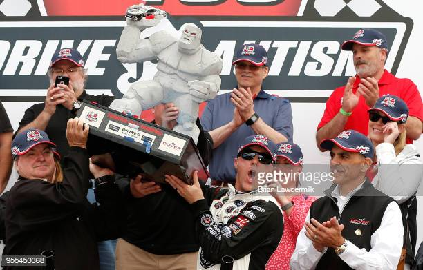 Kevin Harvick driver of the Jimmy John's Ford celebrates with the trophy in victory lane after winning the Monster Energy NASCAR Cup Series AAA 400...