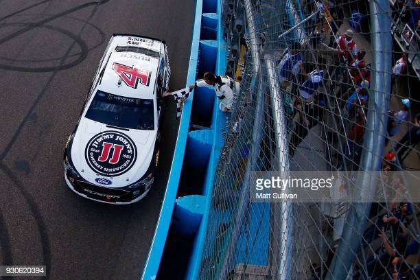 Kevin Harvick driver of the Jimmy John's Ford takes the checkered flag from the NASCAR official after winning the Monster Energy NASCAR Cup Series...