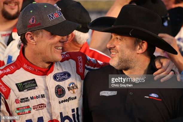 Kevin Harvick driver of the Mobil 1 Ford and team owner Tony Stewart celebrate in Victory Lane after winning the Monster Energy NASCAR Cup Series AAA...