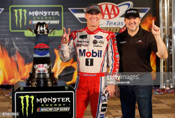 Kevin Harvick driver of the Mobil 1 Ford and Tony Stewart coowner of StewartHaas Racing pose with the trophy in Victory Lane after winning the...
