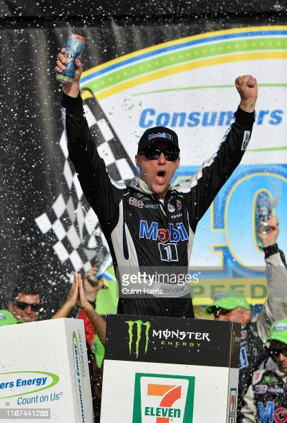 Kevin Harvick, driver of the Mobil 1 Ford, celebrates in Victory Lane after winning the Monster Energy NASCAR Cup Series Consumers Energy 400 at...