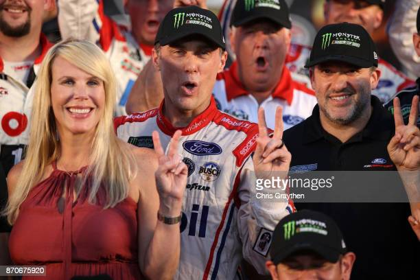 Kevin Harvick driver of the Mobil 1 Ford celebrates in Victory Lane with his wife Delana and Tony Stewart coowner of StewartHaas Racing following the...