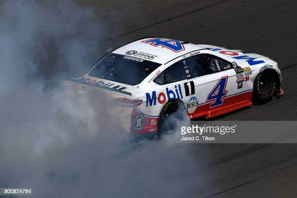Kevin Harvick driver of the Mobil 1 Ford celebrates with a burnout after winning the Monster Energy NASCAR Cup Series Toyota/Save Mart 350 at Sonoma...