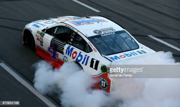 Kevin Harvick driver of the Mobil 1 Ford celebrates with a burnout after winning the Monster Energy NASCAR Cup Series AAA Texas 500 at Texas Motor...