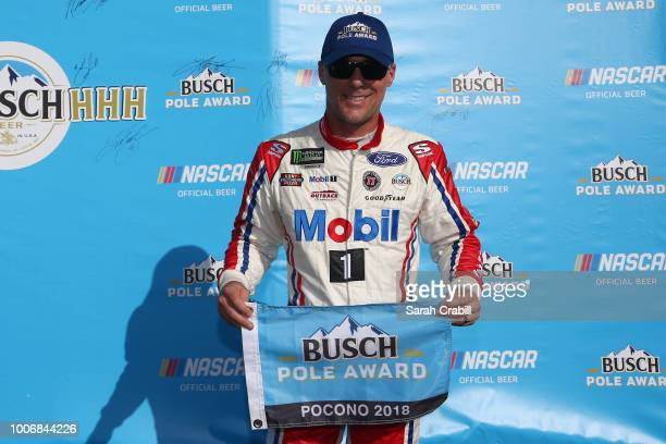 Kevin Harvick driver of the Mobil 1 Ford poses with the Busch Pole Award after posting the fastest lap during qualifying for the Monster Energy...