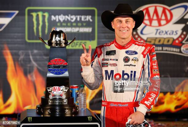 Kevin Harvick driver of the Mobil 1 Ford poses with the trophy in Victory Lane after winning the Monster Energy NASCAR Cup Series AAA Texas 500 at...