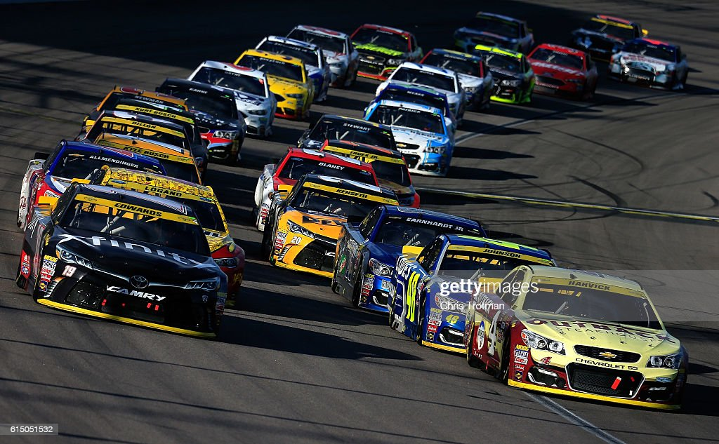 Kevin Harvick, driver of the #4 Outback Chevrolet, and Carl Edwards, driver of the #19 Xfinity Toyota, lead the field to the final restart during the NASCAR Sprint Cup Series Hollywood Casino 400 at Kansas Speedway on October 16, 2016 in Kansas City, Kansas.