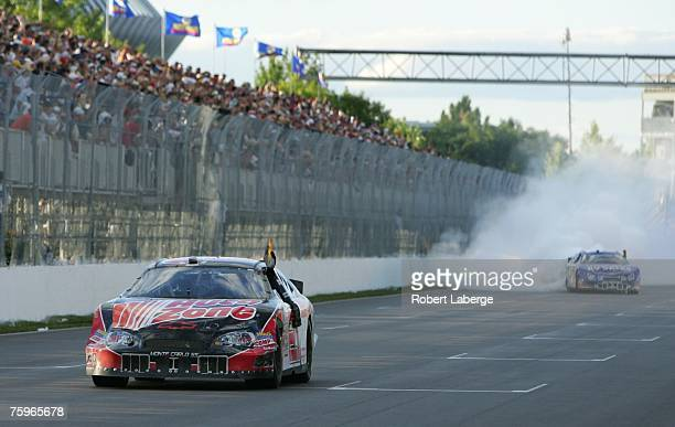 Kevin Harvick driver of the Richard Childress Racing AutoZone Chevrolet drives winning the NASCAR Busch Series NAPA Auto Parts 200 as Robby Gordon...