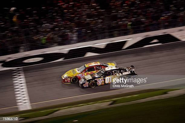 Kevin Harvick driver of the Shell/Pennzoil Chevrolet leads Mark Martin driver of the US Army Chevrolet right before crossing the finish line to...