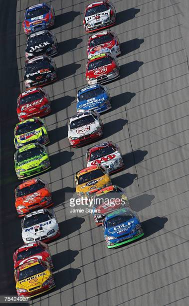 Kevin Harvick driver of the Shell/Pennzoil Chevrolet leads Tony Raines driver of the DLP HDTV Chevrolet Reed Sorenson driver of the Target/Maxwell...