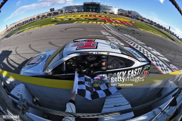 Kevin Harvick StewartHaas Racing Ford Fusion drives along the safer barrier to grab the Sunoco checkered flag to celebrate the victory during the...