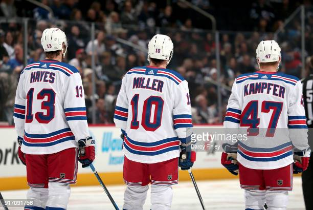 Kevin Hayes JT Miller and Steven Kampfer of the New York Rangers stand on the ice during the singing of the National anthems prior to puck drop...
