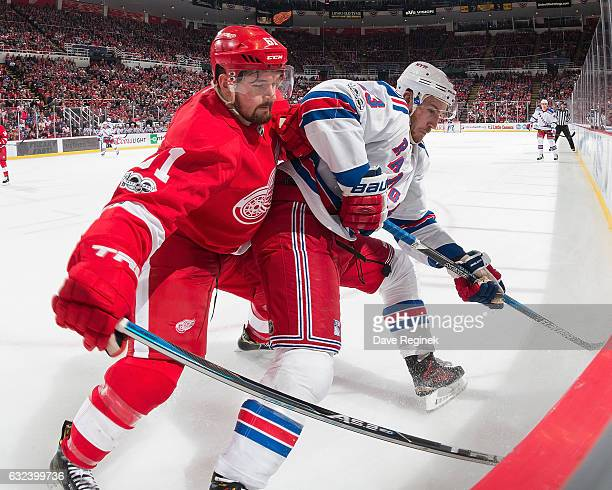 Kevin Hayes of the New York Rangers battles along the boards with Xavier Ouellet of the Detroit Red Wings during an NHL game at Joe Louis Arena on...