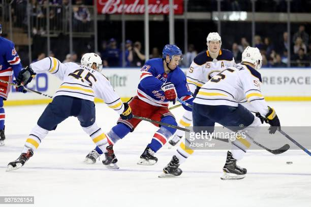 Kevin Hayes of the New York Rangers reaches for the puck against Brendan Guhle and Rasmus Ristolainen of the Buffalo Sabres in the second period...