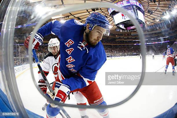 Kevin Hayes of the New York Rangers skates against John Moore of the New Jersey Devils at Madison Square Garden on December 18 2016 in New York City...