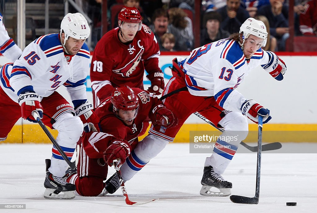 Kevin Hayes #13 of the New York Rangers skates with the puck ahead of Tobias Rieder #8 of the Arizona Coyotes during the third period of the NHL game at Gila River Arena on February 14, 2015 in Glendale, Arizona.