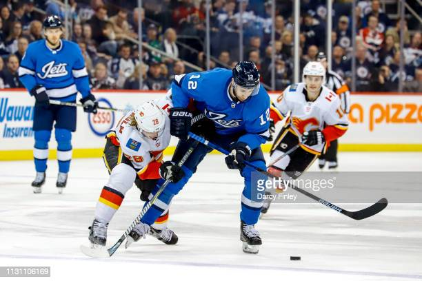 Kevin Hayes of the Winnipeg Jets battles Elias Lindholm of the Calgary Flames for the loose puck during second period action at the Bell MTS Place on...