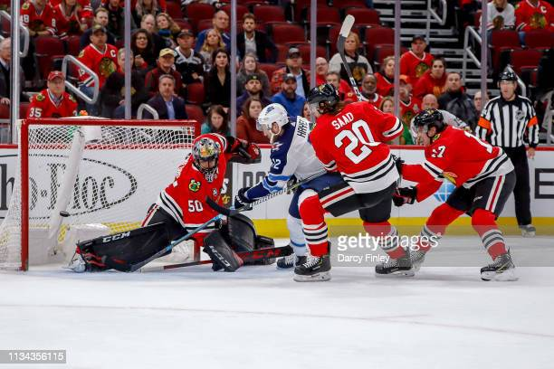 Kevin Hayes of the Winnipeg Jets gets around defenders Brandon Saad and Dylan Strome of the Chicago Blackhawks as he scores the overtime winner...
