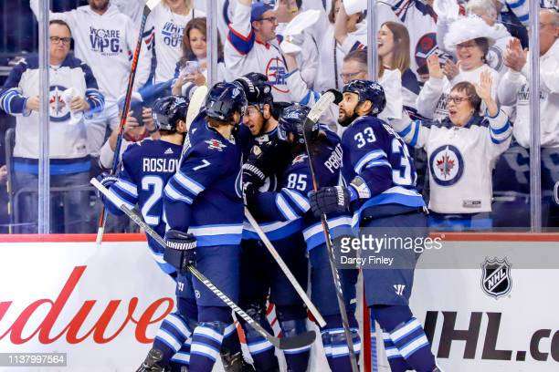 Kevin Hayes of the Winnipeg Jets gets congratulated by teammates Jack Roslovic Ben Chiarot Mathieu Perreault and Dustin Byfuglien following a first...