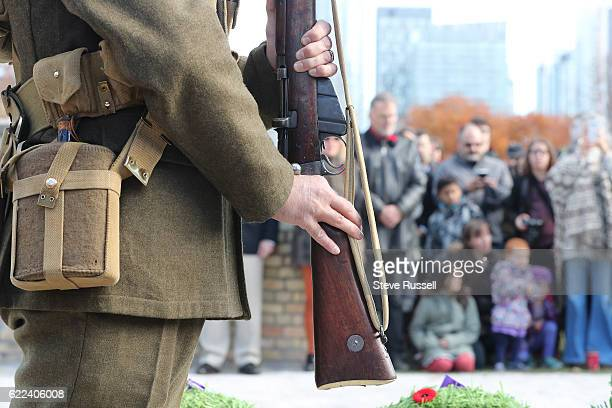 TORONTO ON NOVEMBER 11 Kevin Hebib holds a rifle at a Remembrance Day ceremony held in the Military Burial ground just outside Fort York in Toronto...