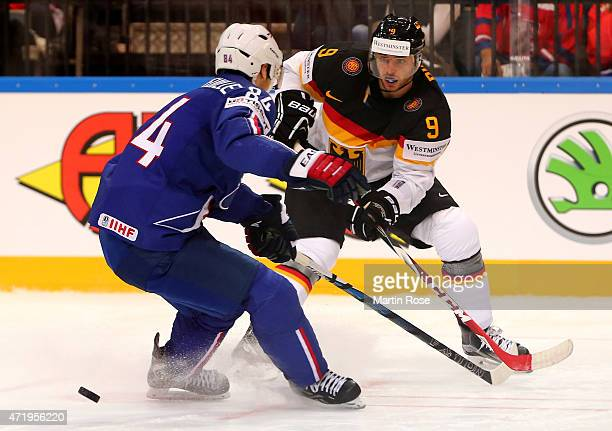 Kevin Hecquefeuille of France and Tobias Rieder of Germnay battle for the puck during the IIHF World Championship group A match between France and...