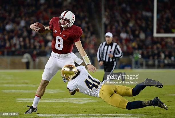 Kevin Hogan of the Stanford Cardinal gets tackled short of a first down by Matthias Farley of the Notre Dame Fighting Irish during the third quarter...