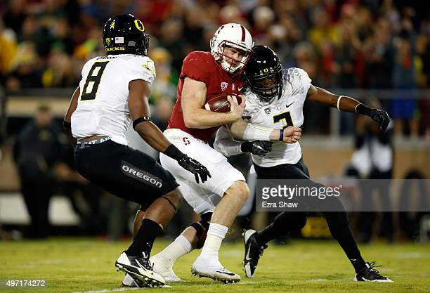 Kevin Hogan of the Stanford Cardinal is hit by Tyree Robinson of the Oregon Ducks but still runs the ball in for a touchdown while Reggie Daniels of...
