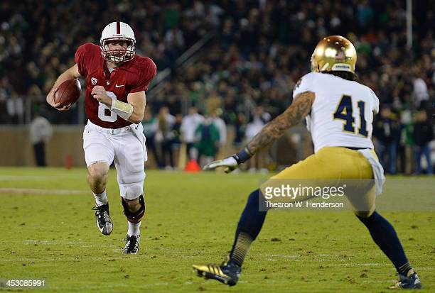 Kevin Hogan of the Stanford Cardinal scrambles with the ball, pursued by Matthias Farley of the Notre Dame Fighting Irish during the third quarter at...