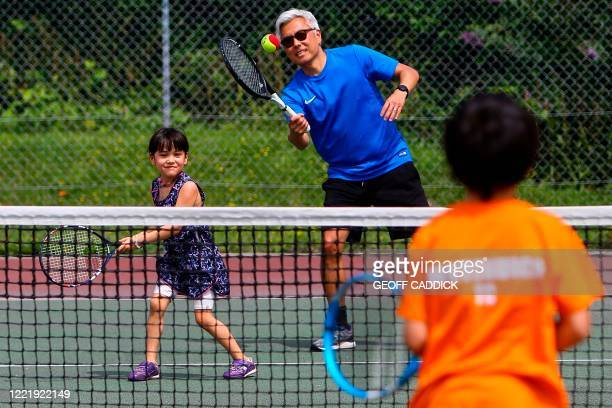 Kevin Hong plays tennis with his children Ailsa and Euan at Whitchurch Tennis Club in Cardiff on June 22, 2020 as the Welsh government begins to ease...