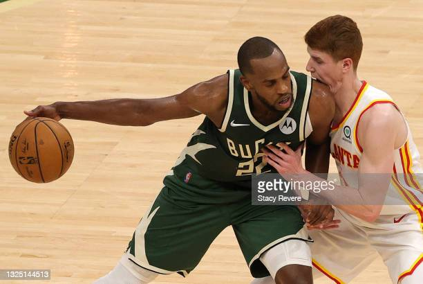 Kevin Huerter of the Atlanta Hawks takes a shoulder to the jaw while defending Khris Middleton of the Milwaukee Bucks during the second quarter in...