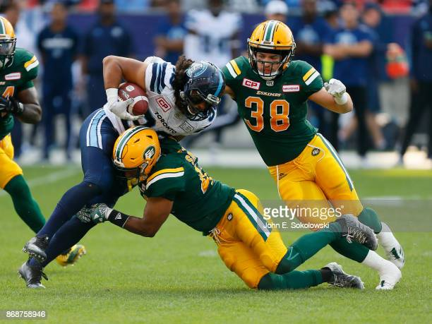 Kevin Jackson and Adam Konar of the Edmonton Eskimos tackle Declan Cross of the Toronto Argonauts during a game at BMO field on September 16 2017 in...
