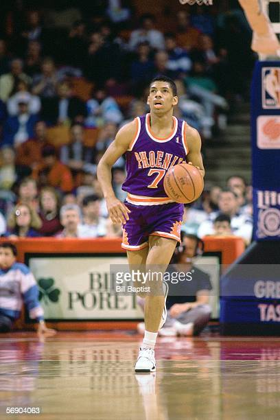 Kevin Johnson of the Phoenix Suns checks the clock as he dribbles upcourt against the Houston Rockets during an NBA game at the Summit circa 1990 in...