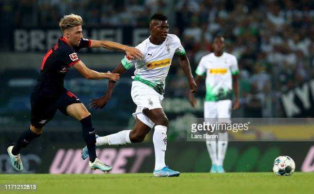 Kevin Kampl of Leipzig challenges Breel Embolo of Moenchengladbach during the Bundesliga match between Borussia Moenchengladbach and RB Leipzig at...