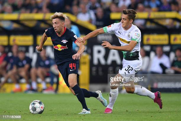 Kevin Kampl of RB Leipzig competes for the ball with Florian Neuhaus of Borussia Monchengladbach during the Bundesliga match between Borussia...