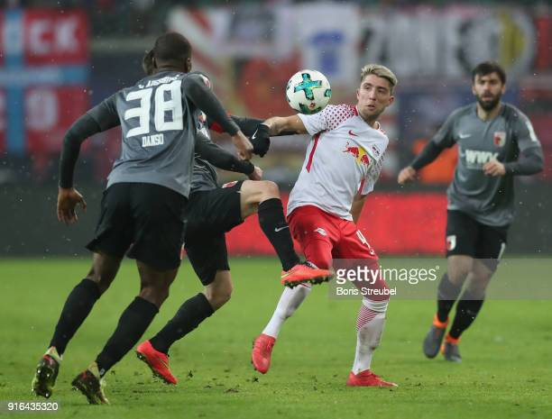 Kevin Kampl of RB Leipzig is challenged by Kevin Danso of FC Augsburg during the Bundesliga match between RB Leipzig and FC Augsburg at Red Bull...