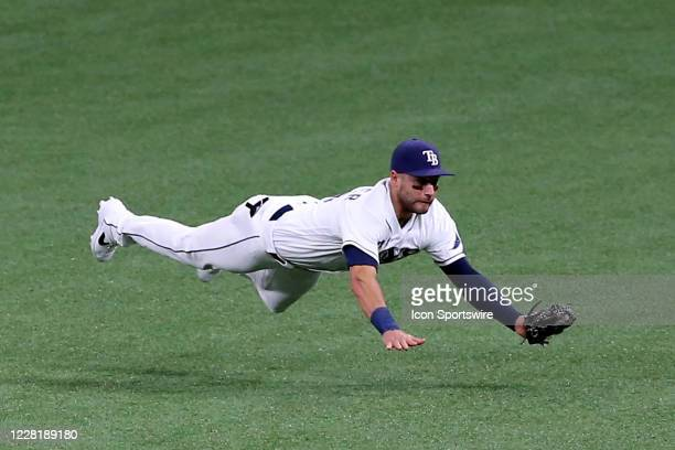 Kevin Kiermaier of the Rays leaps to make a diving catch and flys over the turf before landing safely with the catch during the game between the...