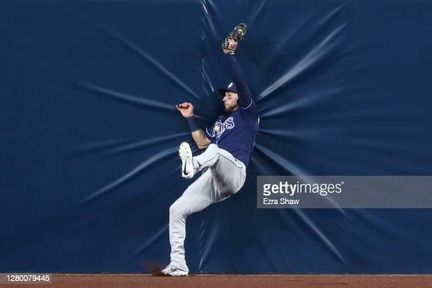 Kevin Kiermaier of the Tampa Bay Rays falls into the outfield wall to steal a home run from Alex Bregman of the Houston Astros during the first...