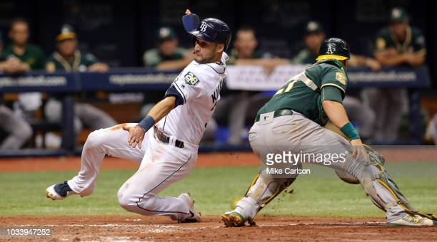 Kevin Kiermaier of the Tampa Bay Rays slides past the tag of Jonathan Lucroy of the Oakland Athletics to score on a sacrifice fly from Jake Bauers in...