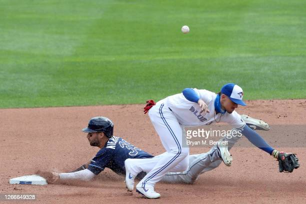 Kevin Kiermaier of the Tampa Bay Rays steals second base as Cavan Biggio of the Toronto Blue Jays misses the throw during the eighth inning of an MLB...