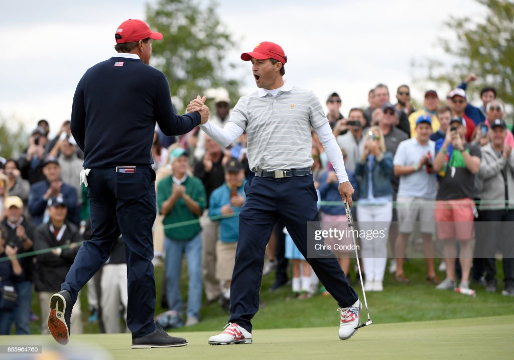 Kevin Kisner celebrates with teammate Phil Mickelson of the U.S. Team after winning 2 and 1 on the 17th hole during the Saturday morning foursomes matches during the third round of the Presidents Cup at Liberty National Golf Club on September 30, 2017, in Jersey City, New Jersey.