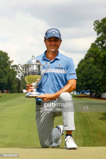 Kevin Kisner of the United States celebrates with the trophy after winning a 6-way sudden-death playoff during the final round of the Wyndham...