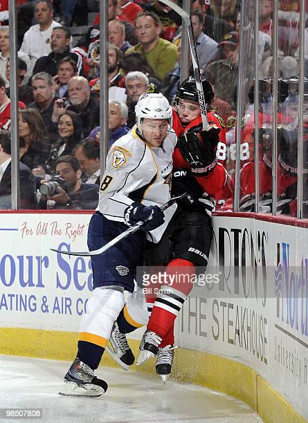 Kevin Klein of the Nashville Predators checks Patrick Kane of the Chicago Blackhawks into the boards at Game One of the Western Conference...