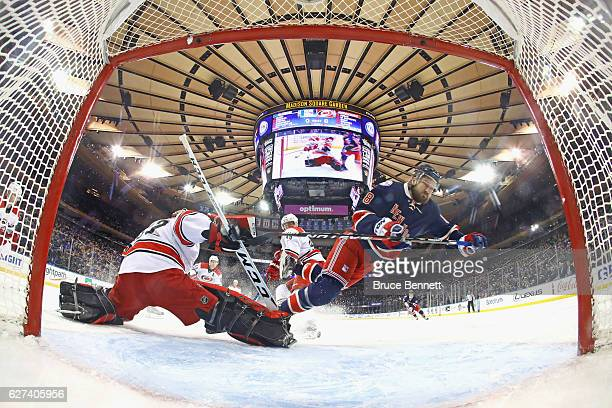 Kevin Klein of the New York Rangers is tripped up by Michael Leighton of the Carolina Hurricanes during the first period at Madison Square Garden on...
